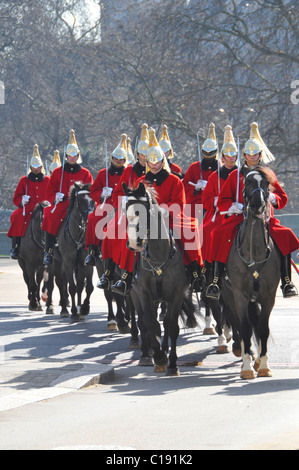 Soldiers & horses of The Life Guards mounted regiment of Household Cavalry in winter ceremonial cloaks uniform riding - Stock Photo