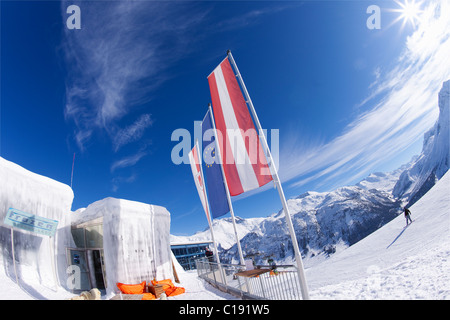 Snow-boarder skiing past the Ice Bar Lech near St Saint Anton am Arlberg in winter snow Austrian Alps Austria Europe - Stock Photo