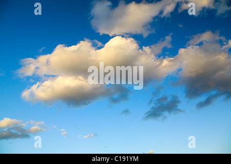 Skyscape of rain clouds against a deep blue sky - Stock Photo