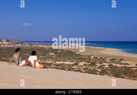 A couple sitting on a sand dune overlooking the Playas de Sotavento beach, Fuerteventura, Canary Islands, Spain, - Stock Photo