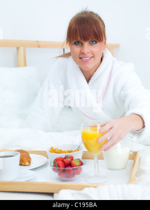 Beautiful woman eating breakfast in bed - Stock Photo