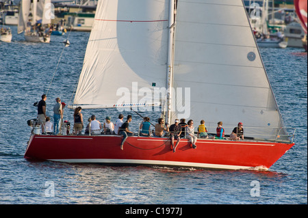 Boat filled with people during Duck Dodge Sailboat Race on Lake Union, Seattle, Washington, USA - Stock Photo
