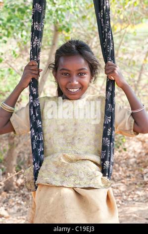 Happy poor lower caste Indian street girl smiling sat in a sari swing. Andhra Pradesh, India - Stock Photo