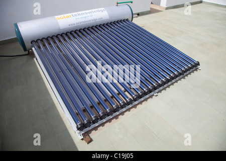 Solar water heating system with tank and evacuated tubes on roof of house Kenya - Stock Photo