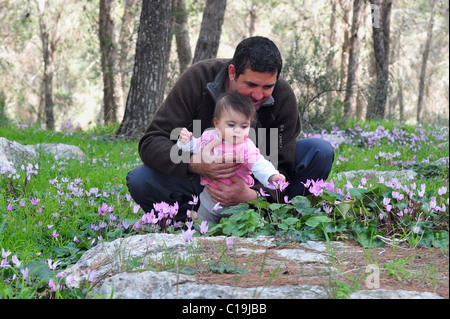 A father and his baby girl child plays with flowers at spring time in the forest. - Stock Photo