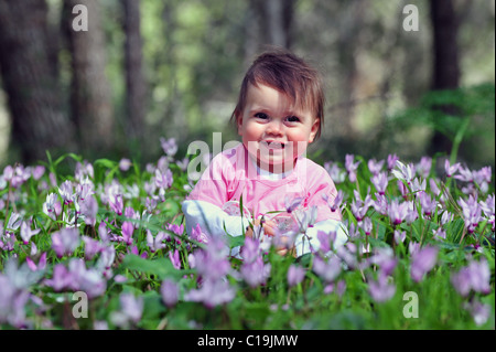 A baby girl child plays with flowers at spring time in the forest. - Stock Photo