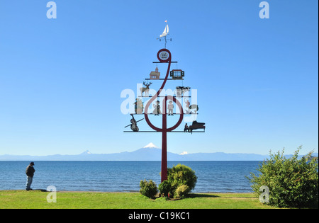 Blue sky view of  man by a Music Festival sign on a green Lake Llanquihue waterfront towards Volcan Osorno, Frutillar, - Stock Photo