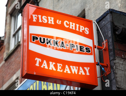A Pukka Pies sign outside a fish & chip shop in a U.K. city. - Stock Photo