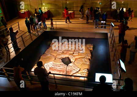 People at the Tlaltecuhtli sculpture exhibit in the Templo Mayor Museum, Mexico City - Stock Photo