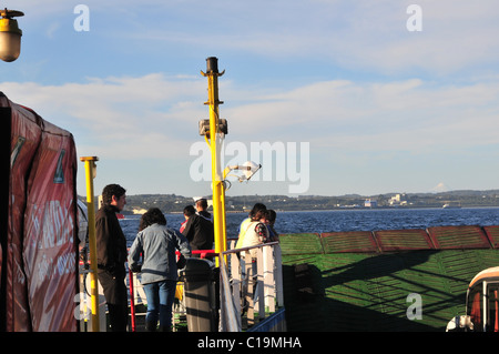 Passengers standing on a pathway balcony above the deck ramp of a Chacao Channel vehicle ferry moving towards Pargua, - Stock Photo