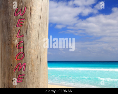 Caribbean tropical beach spell welcome written in wood trunk - Stock Photo