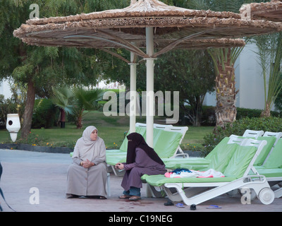 muslim women in burka and headscarfs chat beside swimming pool in Sharm el Sheikh, Egypt - Stock Photo