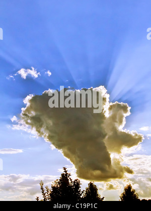 Spectulay Cumulonimbus cloud formation with sun behind projecting light rays. - Stock Photo