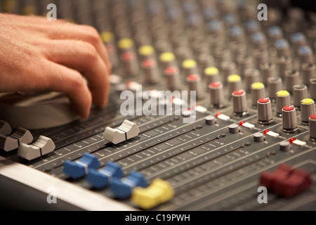 sliders and sound engineers hand on audio mixing desk in a theatre concert hall - Stock Photo