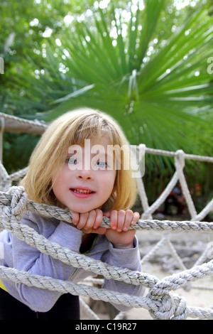 adventure blond happy little girl on jungle park rope bridge - Stock Photo