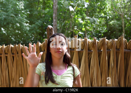 Indian girl waving greeting in jungle south american rainforest - Stock Photo