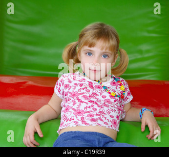 blond little girl resting on colorful playground red and green - Stock Photo