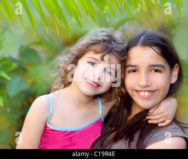 Mixed ethnicity cousin friends hug latin and caucasian in jungle garden - Stock Photo