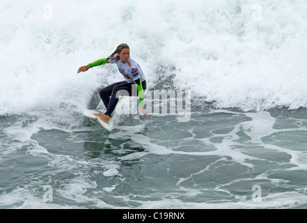 Pro female surfer competing in the 'US Open of Surfing' at Huntington Beach,California USA - Stock Photo