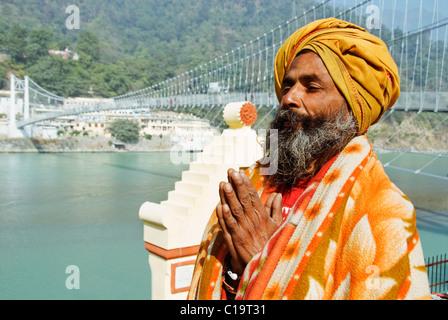 Sadhu praying with Lakshman Jhula in the background, Ganges River, Rishikesh, Uttarakhand, India - Stock Photo