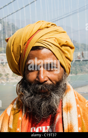 Portrait of a sadhu with a suspension bridge in the background, Lakshman Jhula, Ganges River, Rishikesh, Uttarakhand, - Stock Photo