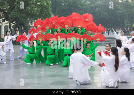 Colourful dancers early on a Sunday morning by Lake Hoan Kiem in the heart of Hanoi, Vietnam - Stock Photo