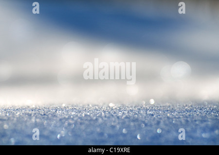 Sparkling white-blue snow background with bright patches of light. It is removed on soft focus. - Stock Photo