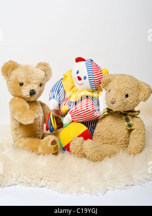 Two traditional teddy bears and a colourful toy clown sitting on a sheepskin rug. A cute celebration image for a - Stock Photo