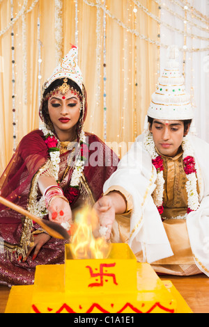 Couple performing Yajna in Bengali wedding - Stock Photo