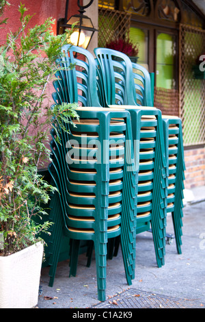 pile of green plastic chairs against the cafe wall on a street - Stock Photo