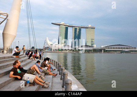 Tourists relaxing on the waterfront with the Marina Bay Sands Singapore in the background.  Marina Bay, Singapore - Stock Photo