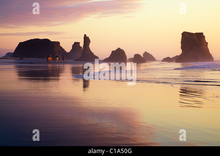 Tourists riding horses on pacific ocean beach in golden sunset, Haystack rocks, cloud reflections in wet sand at - Stock Photo