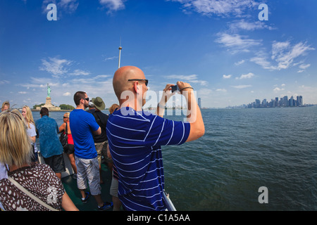 Tourists cruise by Statue of Liberty in New York Harbor taking pictures of Manhattan skyline. - Stock Photo