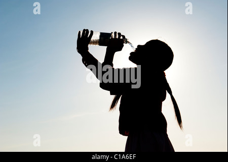 Indian girl drinking mineral water from plastic water bottle. India. Silhouette - Stock Photo