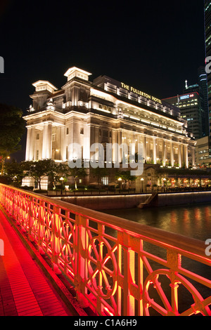 The Fullerton Hotel and Anderson Bridge illuminated at night, Singapore - Stock Photo