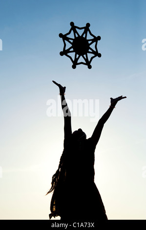 Silhouette indian girl throwing a symbol of one world, unity and humanity into the air. India - Stock Photo