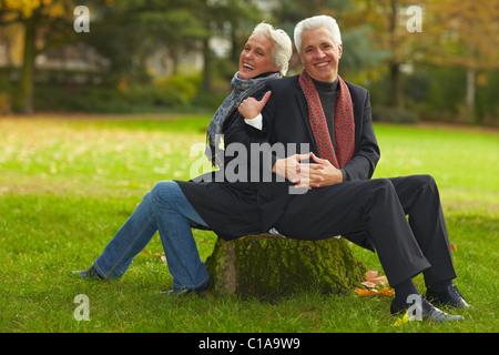 Couple sitting on tree trunk - Stock Photo