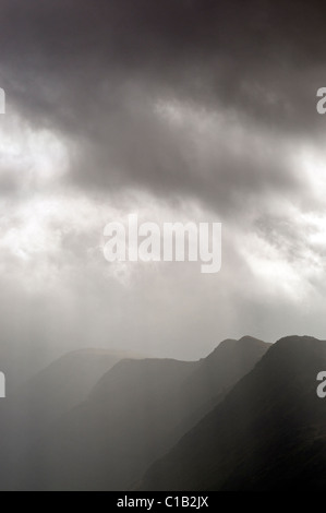 The main Llechog ridge on Snowdon, shrouded in cloud and rays of sunshine - Stock Photo