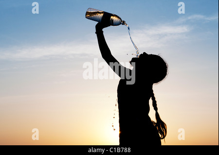 Indian girl drinking mineral water from plastic water bottle at sunset. India. Silhouette - Stock Photo