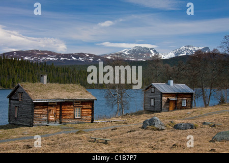 Log cabin with sod roof along lake at Fatmomakke, Lapland, Sweden - Stock Photo