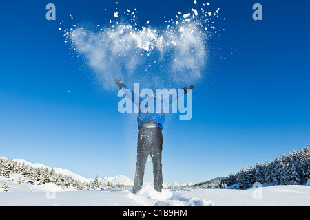 A male hiker on snowshoes in Alaska throws up snow into the air expressing joy at the sunny day and mountain scenery. - Stock Photo