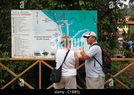 A guide talks with a tourist in front of a map at the entrance to Manuel Antonio National Park, Costa Rica - Stock Photo