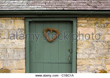 Wicker heart on grey painted stable door of old slate roofed building at Easton Walled Gardens, Grantham, Lincolnshire, - Stock Photo