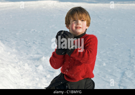 Cute ginger haired boy ready to throw a snow ball on a winter day