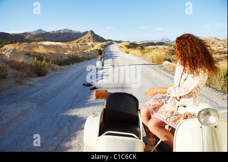 Woman picking up clothes from the road - Stock Photo