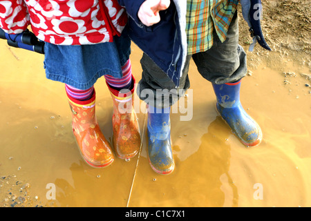Brother and Sister standing in  Muddy Puddles - Stock Photo