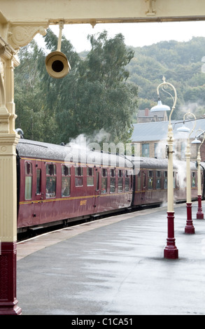 Steam train pulls in to keighley train station - Stock Photo