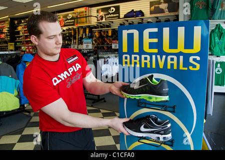 Athletic supply store manager arranges sports clothing placement in athletic sports store - Stock Photo