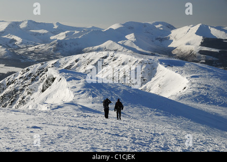 Walkers on the summit ridge of snow covered Blencathra in winter in the English Lake District. Derwent Fells in - Stock Photo