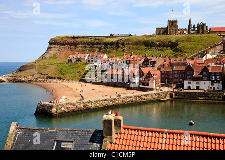 Whitby Harbor on a sunny day with the Abbey on the hill top over looking the town - Stock Photo